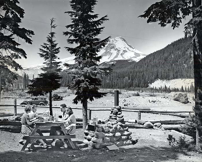 Four young adults, 2 women, 2 men, sit at a picnic table eating a meal. Mt Hood's snowy peek shows in the background.