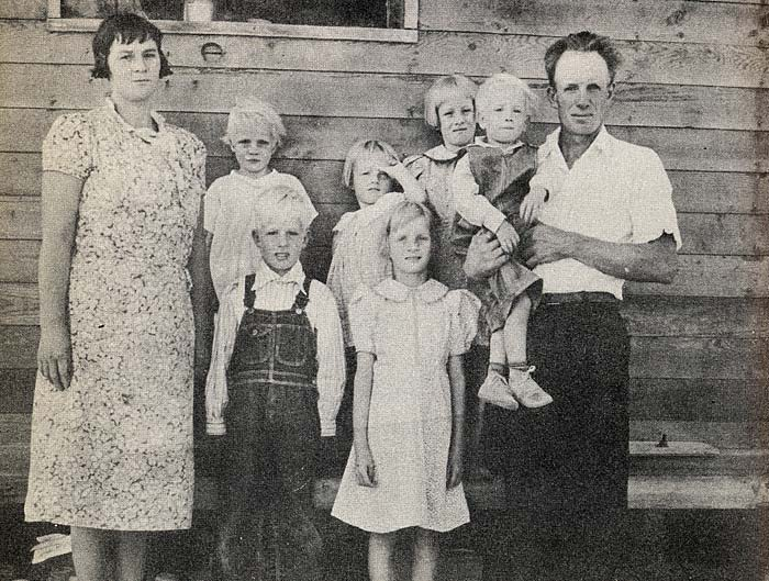 Family of 8 stand in front of wood plank house: mother, father and 6 children.