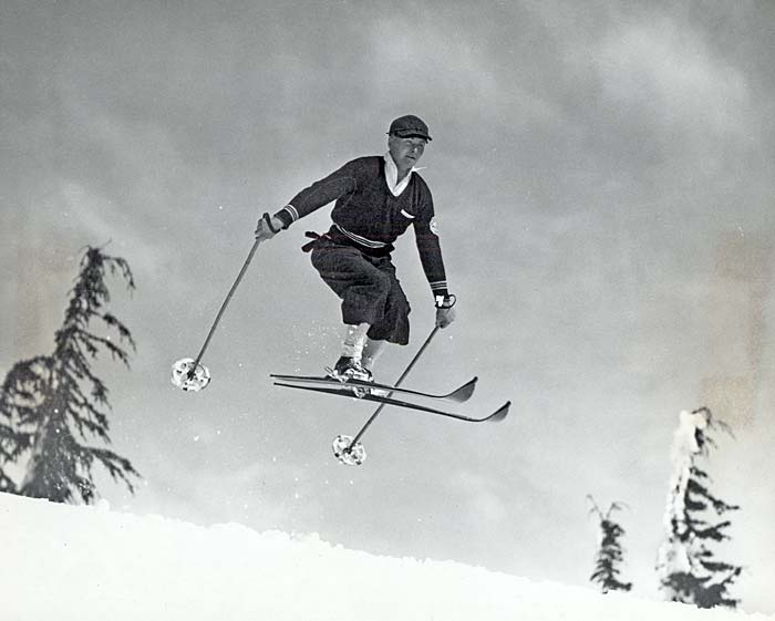 Skier in mid jump over a snowy hilltop. The tops of evergreen trees are seen in the background.