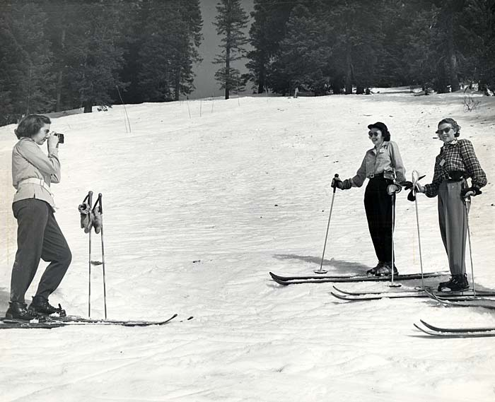 Three female skiers in the Tollgate area. Two women pose while the other takes a photo.