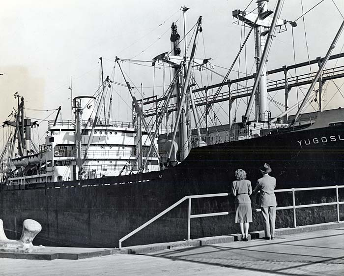 A man and a woman stand on the sidewalk holding on to a railing and looking at a large ship.