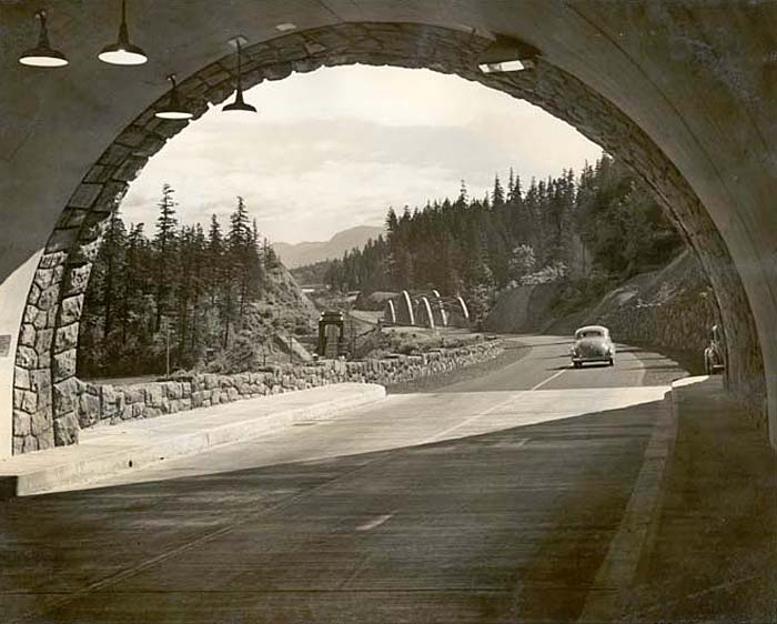Stone tunnel opens up on highway with a 1940s car driving away.