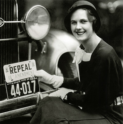 "Stylish woman in white gloves and a cloche hat holds ""Repeal 18th Amendment"" license plate over a real license plate of a car."