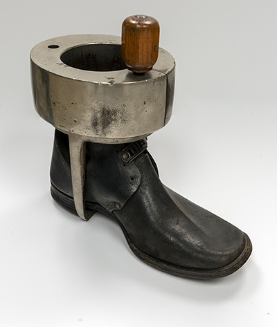 A boot with a metal brace fitting around the ankle and hooked under the heal.