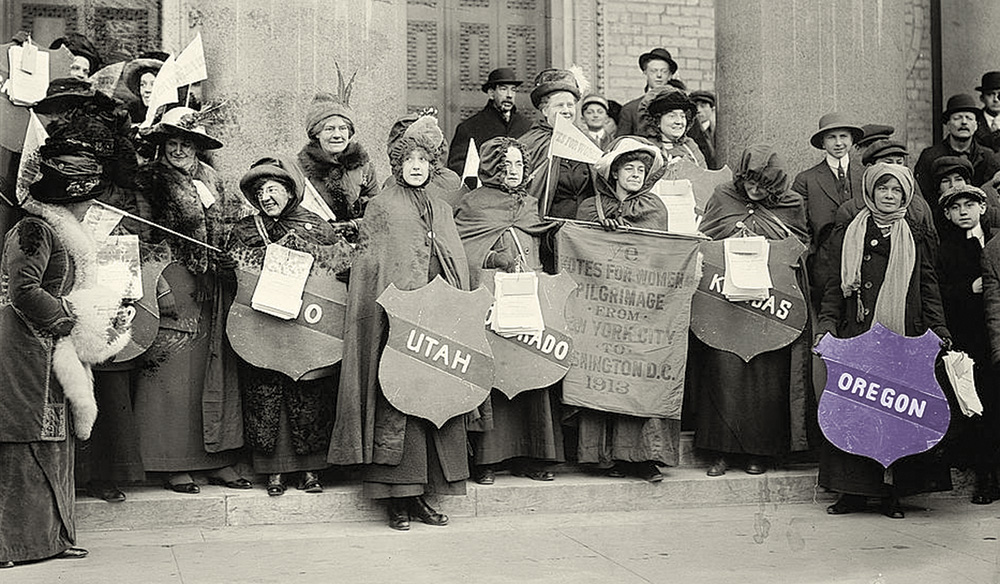More than a dozen women dressed for cold weather stand on the steps of a building. They carry signs with the names of their states and suffrage messages.