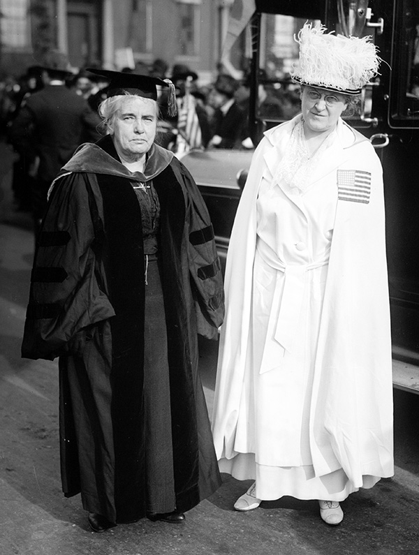 Photo of Carrie Chapman Catt in dark robes & Anna Howard Shaw in white robes.