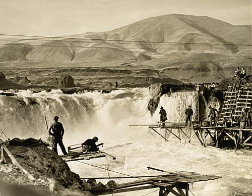 Men stand on platforms over Celilo falls on the Columbia River, fishing.