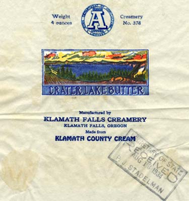"Crater Lake drawing with evergreen trees on shore & a sun set. Reads ""Crater Lake Butter manufactured by Klamath Falls Creamery"""