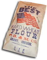 "A sack with an American flag & the words ""The Best Hard wheat Flour, P.D. & M. Co. Grant, Oregon."""