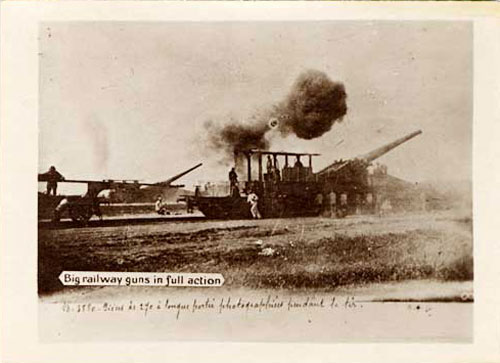 """Big railway guns in full action"" printed on photo. Large artillery gun fires and a cloud of dark smoke shows out the barrel."