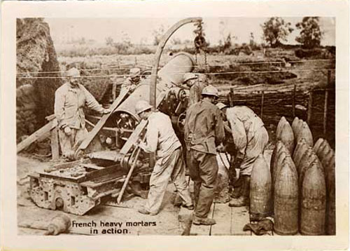 Four men operate a mortar piece with 3ft tall shells to the right.