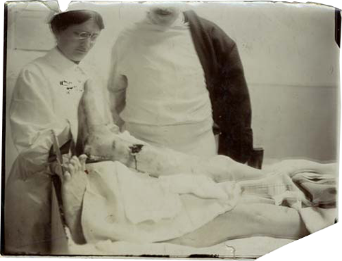 A nurse and doctor look over the leg wound on a soldier.