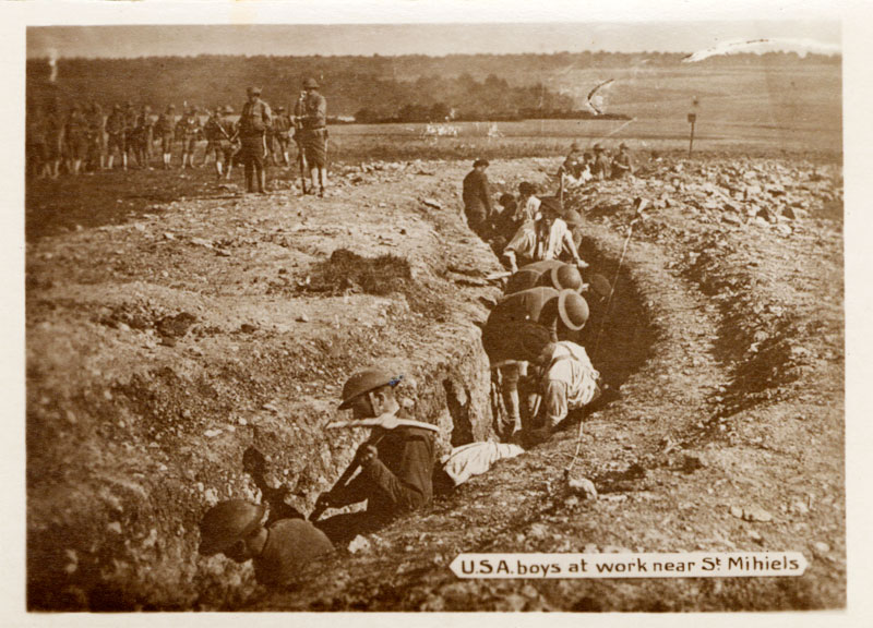 A dozen men in a trench with pick axes work while other men above look on.