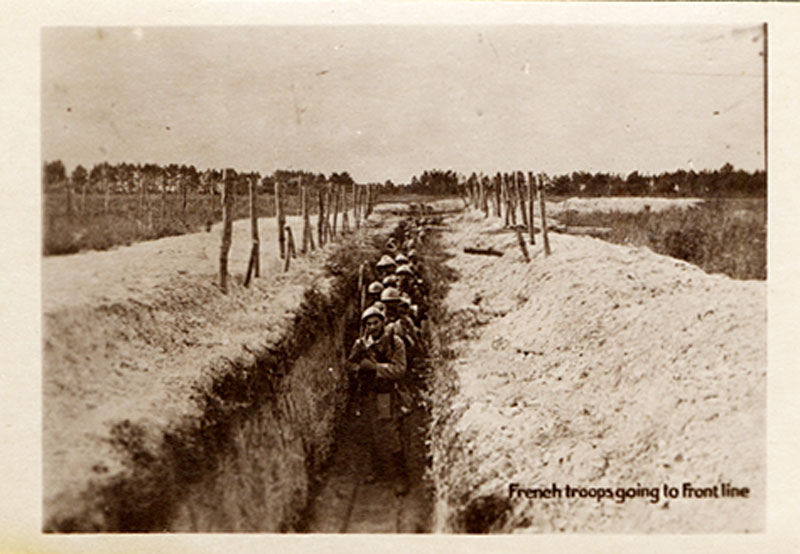 Trench viewed from one end looks downward at a long row of men in helments and combat uniforms.