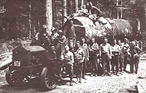 Log truck with about 16 men gathered around stands in the forest loaded with logs.