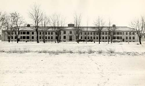 Eastern Oregon State Hosptial shown in winter with bare trees in front and snow covering ground.