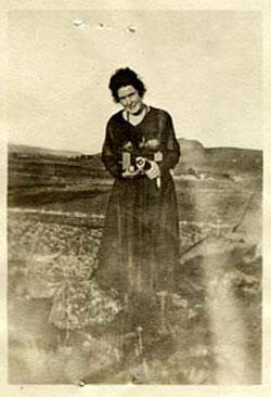 Enid MKern stands outside holding what looks like a camera, circa 1918.