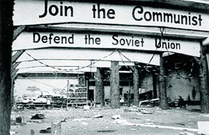 "Archway reads ""Join the Communist, Defend the Soviet Union"" in a rundown, ruin structure."