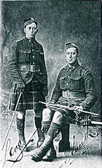 Two men in kilts, one man standing, one sitting, pose for picture.