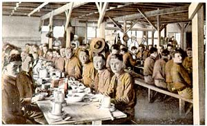 Dozens of soldiers sitting in a mess hall eating a meal.