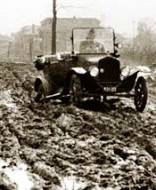 Model T Ford driving on muddy road with bad ruts
