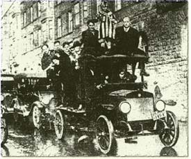 Eight people pile into and on top of a model T car to drive through the street in celebration.