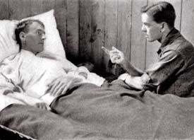 Soldier lies in hospital bed talking to therapist.
