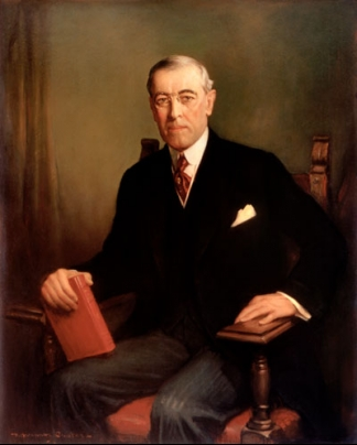 Woodrow Wilson in a tie and suit sits in a chair and holds a book in his hands.