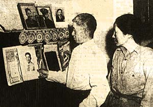 Japanese American man & woman look at photos on a wall in their home.