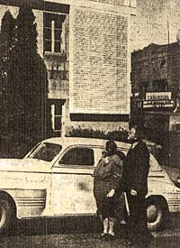 Woman & man stand next to a car outside the county courthouse and look at the honor roll on the wall.