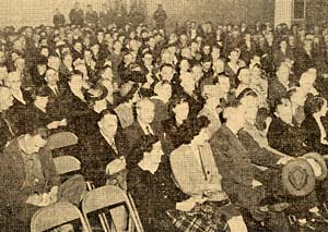 Hundreds of people sit in a crowded room in folding chairs.