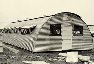 A quonset hut. A lightweight prefabricated structure of corrugated galvanized steal with semicircular roof.