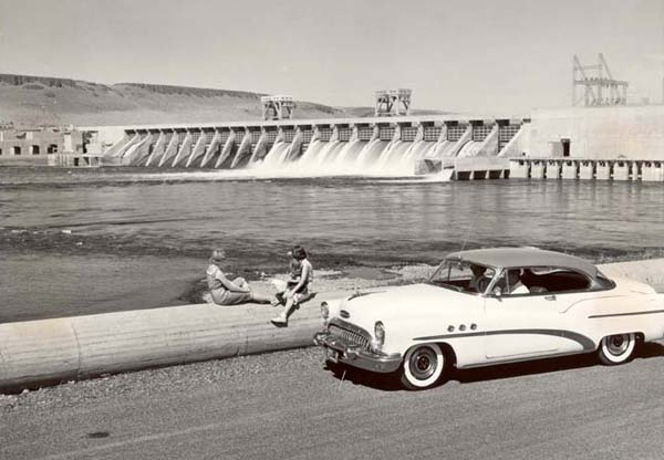 2 women sit on a wall on the bank of a river. The McNary Dam is in the distance.