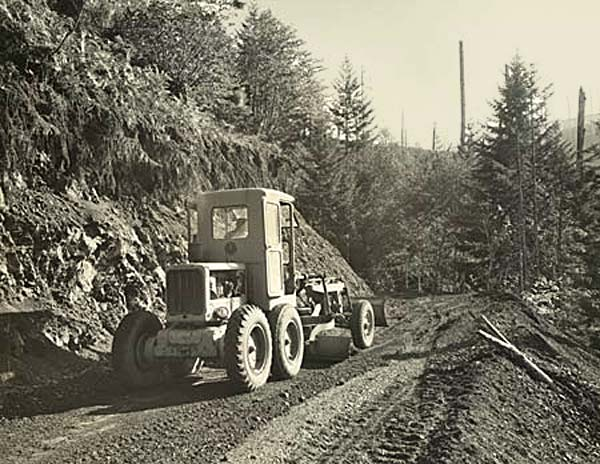 A piece of road making equipment like a tractor sits on a gravel road.