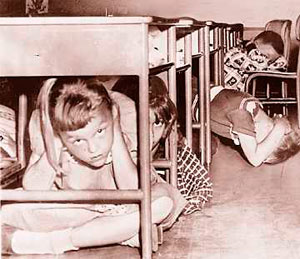 Photo of children crouching under their desks & covering heads with hands.