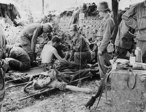 Photo of wounded soldiers on stretchers while others care for them in the field.