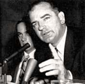 Photo of Senator McCarthy speaking into microphone. One hand is raised with a finger up like he's making a point.