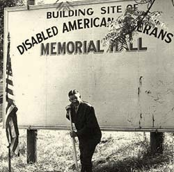 "Gov. McKay with a shovel posing in front of sign that reads ""Building site of disabled American Veterans memorial hall"""