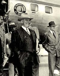President Truman in suit and cowboy hat stands with other men outside an airplane.