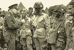 Gen. Eisenhower talks with a group of dozens of soldiers in the field.