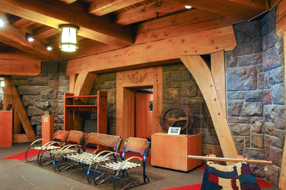Stone walls and heavy wooden beams of the Timberline Lodge. Hand crafted chairs and other adornments.