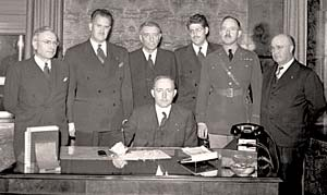 Seven men of the Oregon State Defense Council gather around a desk for a photo..