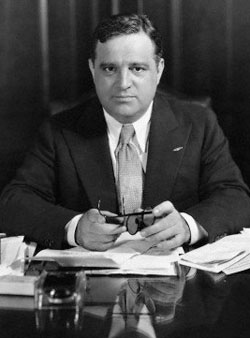Photo of Fiorello La Guardia in suit and tie sitting at desk with papers and books in front of him. He holds eye glasses.