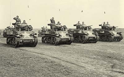 Line of 4 tanks with men atop.
