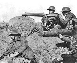 Photo of soldiers sitting on the ground an manning a large gun on a stand.