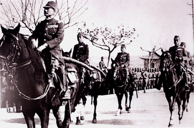 Japanese men on horses ride past lines of soldiers.