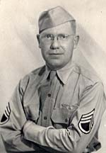 Photo of Bill DeCew in military uniform. He's wearing glasses & has arms crossed in front.