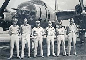 "6 men in military uniforms stand in front of a bomber aircraft with ""L"" and the number 14 printed on side."