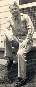 Photo of Sidney Hoffman in military uniform sitting on brick step outside a building.