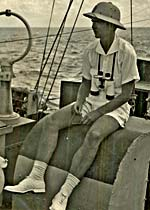 Man in pith hat, shorts, t-shirt sits on a boat. He has binoculars around his neck.